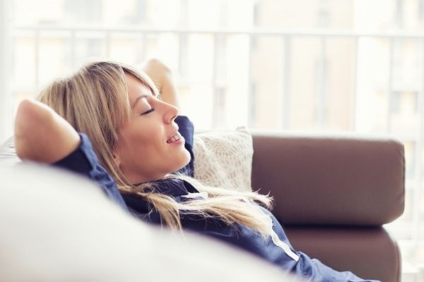 breath better with a new ac installation in maryland. blond woman relaxing inside on her couch after receving a new air conditioner installation.